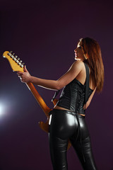 Sexy guitar player over purple background