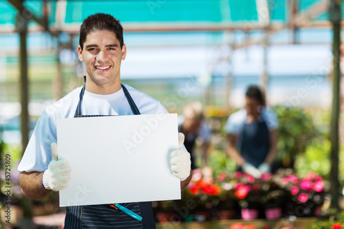 happy gardener holding white board in greenhouse