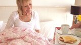 Senior Man Bringing Wife Breakfast In Bed