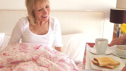 Senior Man Bringing Wife Breakfast In Bed