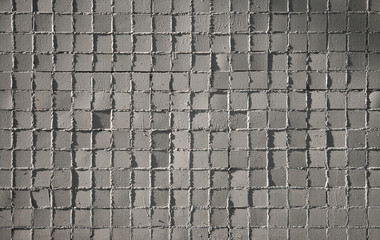 Small gray mosaic tiles on a wall