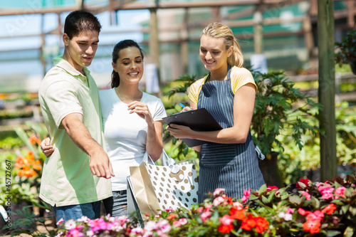 happy couple shopping for plants in greenhouse