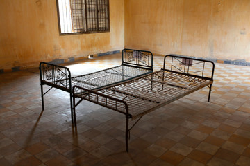 Metal rusty beds in empty prison room, Cambodia