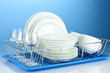 clean dishes on stand on blue background
