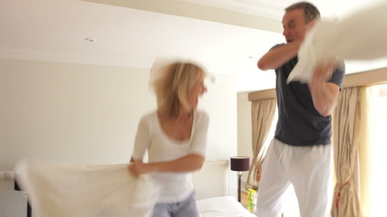Senior Couple Jumping On Bed Having Pillow Fight