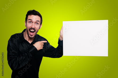 man holding blank white board on yellow backgroud