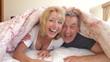 Senior Couple Hiding Under Duvet On Bed