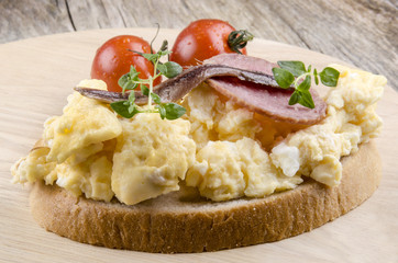 Rührei mit Salami, Sardellen und Tomaten auf Brot