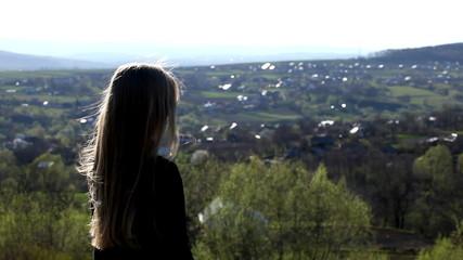A romantic blonde girl looking around her village