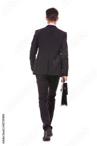 back view of a business man holding a briefcase and walking