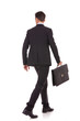 back view of a walking business man with briefcase