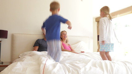 Children Bouncing On Parents Bed