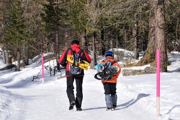 Padre e figlio, escursione sulla neve con snow-shoes