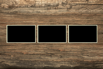Empty photo frames on a weathered wooden background
