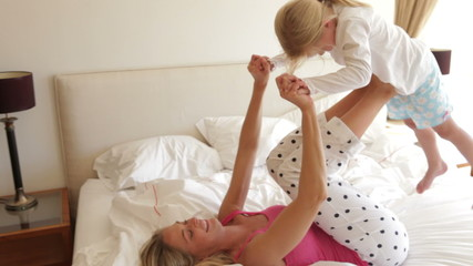 Mother Giving Daughter Ride On Feet Whilst Lying On Bed