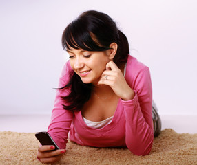 Woman look at phone, lying on the carpet