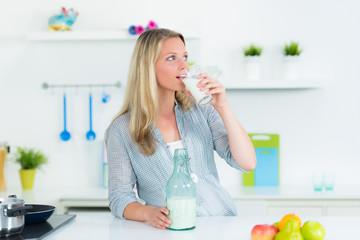 frau in de küche trinkt ein glas milch