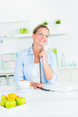 frau führt ein telefongespräch in der küche