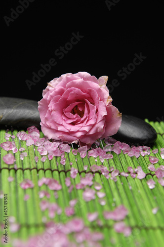 Beautiful pink rose and zen stones with herbal salt in mat