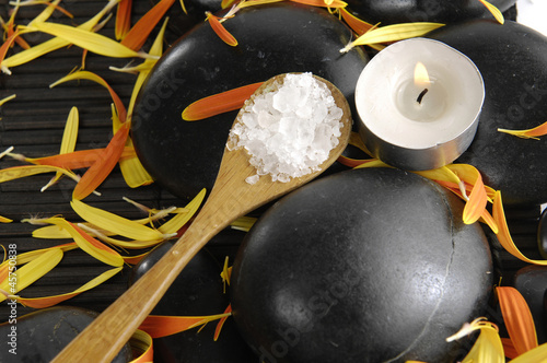 Salt in spoon with flower petals and candle