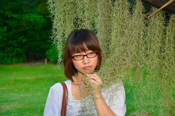 Cute Thai girl examining a Spanish Moss plant