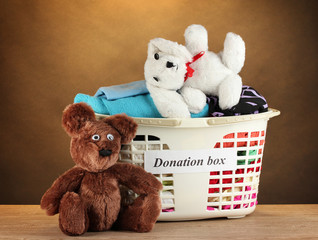 Donation box with clothing on brown background close-up