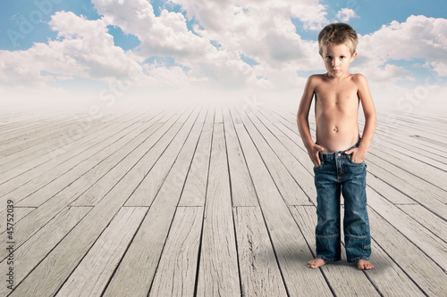 Young kid standing on a wood floor with cloudy blue sky.