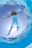 Underwater woman portrait with white dress in swimming pool