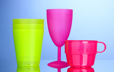 Bright plastic tableware on blue background