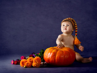 Child with big pumpkin over purple background.