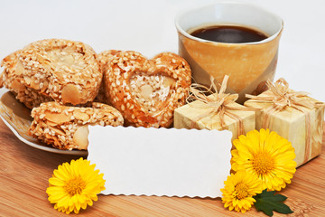 a cup of coffee with cookies, little gifts, yellow flowers