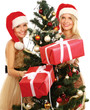 Two girlfriends in santa hat near Christmas tree with gift box