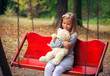 Small beautiful girl embraces an amusing bear