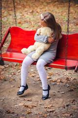 Small beautiful girl embraces an amusing bear