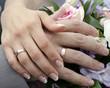 Постер, плакат: Руки молодоженов с обручальными кольцами на букете цветов