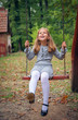 Happy Little Girl Smiling on Swing