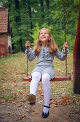 Happy Little Girl Smiling on Swing