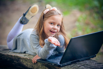 Child in autumn park with laptop