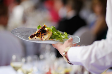 Waitress carrying a plate with meat dish