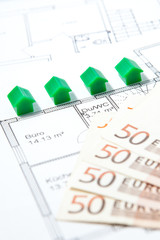 Häuser mit Bauplan und Banknoten