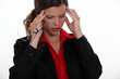 young female executive having migraine
