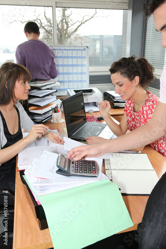 People in an office using a calculator