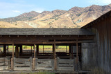Vintage wooden livestock holding pens with mountain background poster