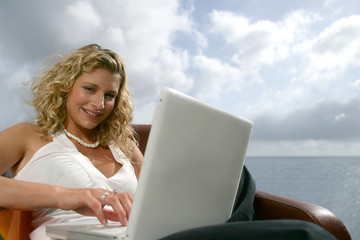 Blonde woman with a computer in front of the sea