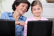 Mother and daughter having fun with their laptops