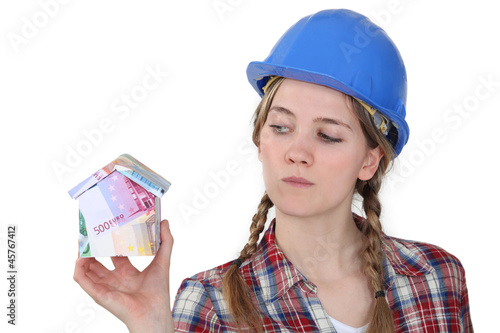 worker holding a miniature of a house made of bills