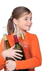Little girl holding empty glass bottles