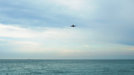 Landing airplane jet fly over sea