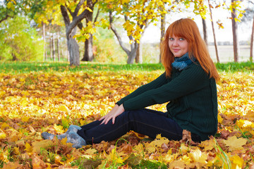 Portrait of a beautiful woman sitting on fall leaves