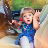 Driving little girl. Beautiful child in a car